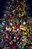 arbre de Noël couvert de neige se tenant à la maison avec les boules et les jouets rouges image stock