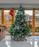 Arbre de Noël décoré des arcs et des babioles d'argent Photos stock