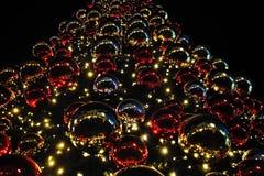 Arbre de Noël décoré des lumières et des sphères colorées image stock