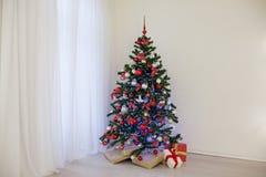 Arbre de Noël dans une salle blanche avec des cadeaux d'une salutation de Noël Photographie stock libre de droits