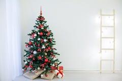 Arbre de Noël dans une salle blanche avec des cadeaux d'une salutation de Noël Photos libres de droits