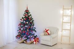 Arbre de Noël dans une salle blanche avec des cadeaux d'une salutation de Noël Photo stock