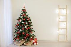 Arbre de Noël dans une salle blanche avec des cadeaux d'une salutation de Noël Images libres de droits