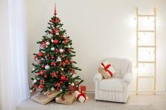 Arbre de Noël dans une salle blanche avec des cadeaux d'une salutation de Noël Photo libre de droits
