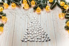 Arbre de Noël des étoiles argentées sur un fond en bois blanc avec la neige et la guirlande Images stock