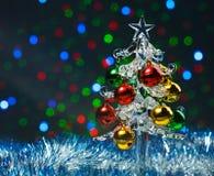 Arbre de Noël en verre avec les boules colorées sur le fond coloré brouillé de lumières Images libres de droits