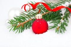 Arbre de Noël et boule rouge sur la neige Photos stock