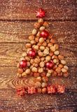 Arbre de Noël fait de noisettes avec les babioles et les cadeaux rouges Photos libres de droits