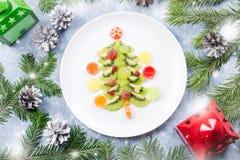 Arbre de Noël fait de gelée de kiwi et de fruit sur un plat avec des branches et des décorations de sapin Vue supérieure, l'espac photographie stock