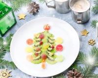 Arbre de Noël fait de gelée de kiwi et de fruit sur un plat avec des branches et des décorations de sapin Vue supérieure, l'espac images libres de droits