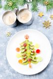Arbre de Noël fait de gelée de kiwi et de fruit sur un plat avec des branches et des décorations de sapin Vue supérieure, l'espac photographie stock libre de droits