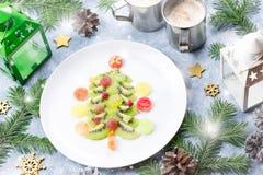 Arbre de Noël fait de gelée de kiwi et de fruit sur un plat avec des branches et des décorations de sapin Vue supérieure, l'espac photos libres de droits