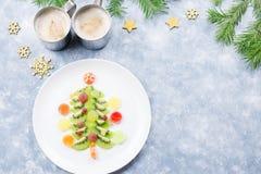 Arbre de Noël fait de gelée de kiwi et de fruit sur un plat avec des branches et des décorations de sapin Vue supérieure, l'espac image libre de droits