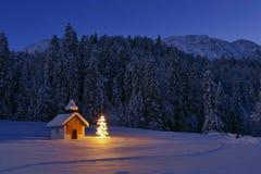 Arbre de Noël lumineux à la chapelle dans le paysage d'hiver, Bavari photos libres de droits