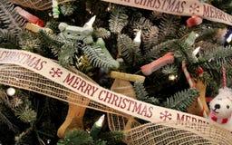 """Arbre de Noël orienté de chiot lunatique couvert de chiens, d'os, et de ruban qui souhaite à un un """"Joyeux Noël ` photo libre de droits"""