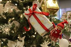 """Arbre de Noël orienté lunatique couvert de filles actuelles et petites enveloppées qui souhaite à une un """"Joyeux Noël ` images libres de droits"""