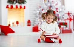 Arbre de Noël proche à la maison de Santa de lettre d'écriture de fille d'enfant images libres de droits