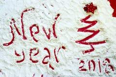Arbre de Noël rouge peint sur la neige et l'inscription : Nouvelle année Image libre de droits