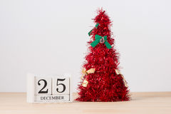 Arbre de Noël rouge sur la table avec calendrier le 25 décembre Image stock