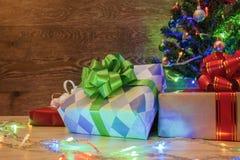 Arbre de Noël sur un fond en bois avec une guirlande et des cadeaux Photo libre de droits