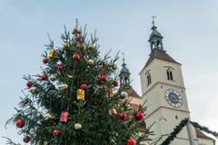 Arbre de Noël sur un marché de Noël à Ratisbonne avec la vue à la nouvelle église paroissiale, Allemagne Images libres de droits