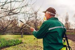 Arbre de pulv?risation d'agriculteur avec le pulv?risateur manuel de pesticide contre le jardin d'insectes au printemps Agricultu photos stock