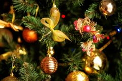 Arbre de sapin de Noël avec les décorations d'or et jaunes : arcs et boules brillantes Concept de vacances d'hiver images stock