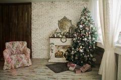 Arbre et cheminée de Noël avec un fauteuil Images stock