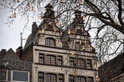 Arbres décorés et lumineux contre les maisons traditionnelles au marché de Noël à Cologne Photo stock