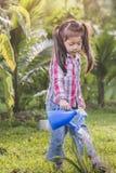 Arbres de arrosage de petite fille asiatique mignonne le soir Photos libres de droits
