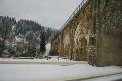 Arbres de Milou de route neigeuse et de forêt d'hiver wallpaper Vieille passerelle image stock