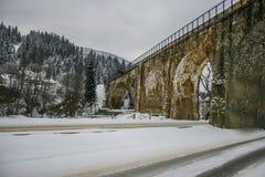 Arbres de Milou de route neigeuse et de forêt d'hiver wallpaper Vieille passerelle photos stock
