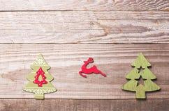 Arbres de Noël en bois simples et renne rouge de vol sur un gree Photo stock