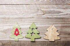 Arbres de Noël en bois simples sur un fond en bois vert Craf Images stock