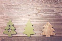Arbres de Noël en bois simples sur un fond en bois vert Craf Image libre de droits