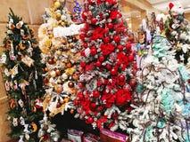 Arbres de Noël multicolores décorés des boules, des fleurs et de t Photos stock