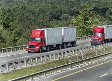 Arbres entourant la route avec des camions Image stock