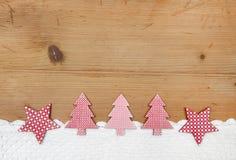 Arbres et étoiles de Noël dans le tissu rouge et blanc sur le dos en bois Images stock
