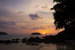 Arbres et silhouettes d'île sur la plage tropicale au coucher du soleil vif t photo libre de droits