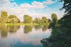 Arbres tranquilles et nuages de rivière Image stock