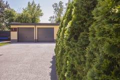 Arbres verts sur la propriété de la maison avec la route de garage et de pierre image libre de droits