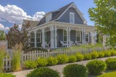 Arbusti e chiusura bianca davanti alle case Fotografia Stock