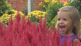 Arbusto floreciente cercano sonriente de la muchacha del niño en el tiempo de primavera almacen de video