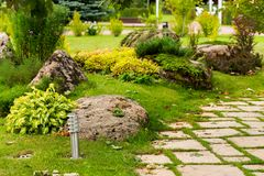 Arbustos e pedras na decoração da paisagem dos canteiros de flores fotografia de stock