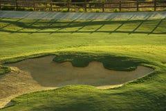 Arcón de la arena en el campo de golf en la salida del sol Imagenes de archivo