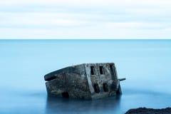 Arcón de la playa de Liepaja Casa del ladrillo, agua suave, ondas y rocas El militar abandonado arruina instalaciones en un mar t Imagen de archivo