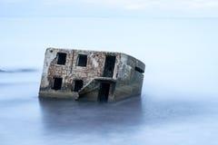 Arcón de la playa de Liepaja Casa del ladrillo, agua suave, ondas y rocas El militar abandonado arruina instalaciones en un mar t Imágenes de archivo libres de regalías