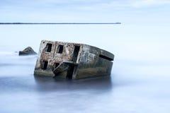 Arcón de la playa de Liepaja Casa del ladrillo, agua suave, ondas y rocas El militar abandonado arruina instalaciones en un mar t Foto de archivo libre de regalías