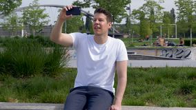 Arc Around a Man Sitting in a Park Filming With a Smartphone 2 stock footage