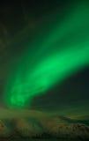 Arc of Aurora polaris. Above a mountain ridge Stock Photo